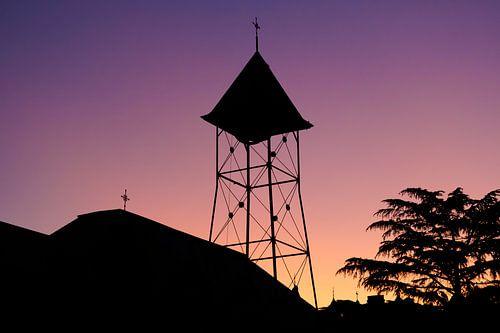 Silhouet van een klokkentoren bij zonsondergang