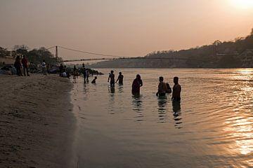 Menschen nehmen bei Sonnenuntergang ein Bad im heiligen Fluss Ganges in Indien von Nisangha Masselink