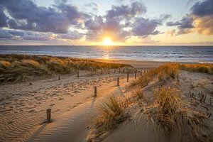zonsondergang aan het strand met wolkenlucht van Dirk van Egmond