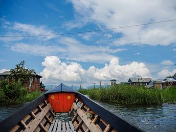 Op een boot in Myanmar (Birma) met zicht op paalwoningen. van Sofie Duchateau