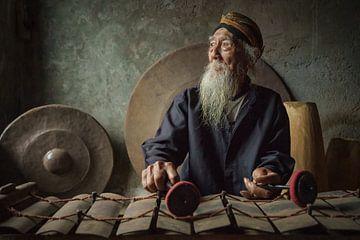 De gamelan maestro Ki Suripto op zijn gamelan in Salatiga, Midden Java, Indonesie van Anges van der Logt