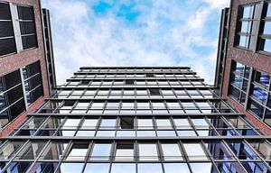 Reflecterende gevel van moderne kantoorgebouwen onder blauwe hemel