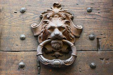 oude metalen deurklopper als leeuwenkop op een rustieke houten deur in italië van Maren Winter