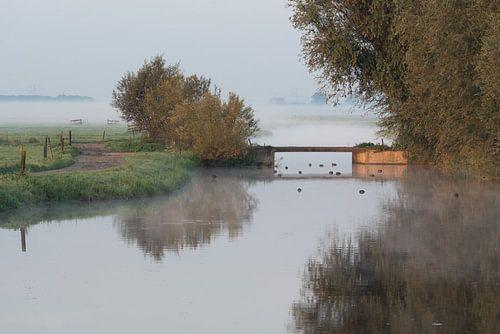 Waterpartij met bruggetje in mistig polderlandschap