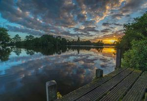 Landschap, zonsopkomst bij steiger met weerspiegeling van wolken in het water