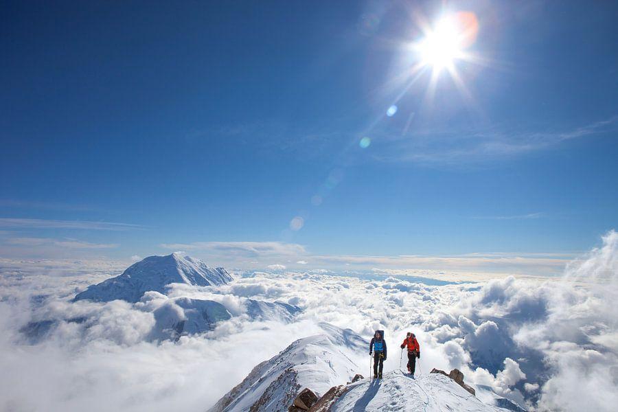 Twee alpinisten boven de wolken op de berg Denali in Alaska van Menno Boermans
