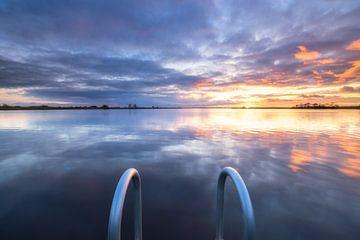 Un coucher de soleil calme sur le Leekstermeer à Groningen. La surface lisse de l'eau donne un beau  sur Bas Meelker