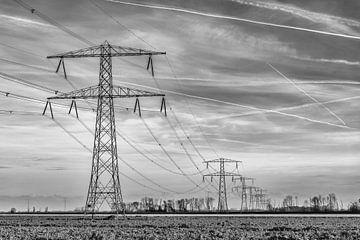 Zwart wit opname van een lange rij hoogspanningsmasten van Ruud Morijn