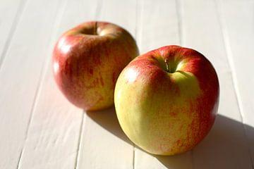 Twee verse jonagold appels op een witte tafel in de zon van Maarten Pietersma