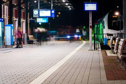 Druk treinstation in de avond