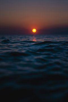De rode zon gaat onder in de blauwe zee van Florian Kunde