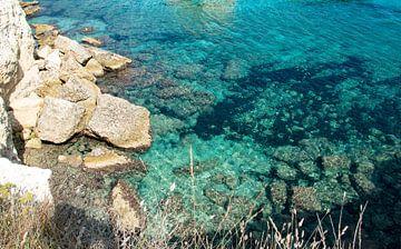 Rotsenpartij met azuurblauw water in Puglia, Italie van Bianca ter Riet