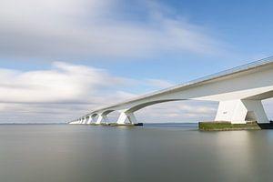 Zeelandbrug lange sluitertijd overdag met blauwe lucht en witte wolken van Margreet Riedstra