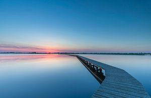 Landschap, wandelpad over het water bij ondergaande zon