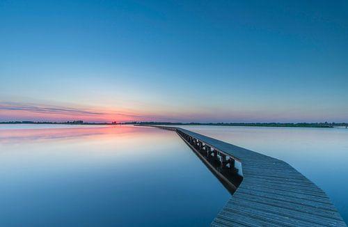 Landschap, wandelpad over het water bij ondergaande zon van