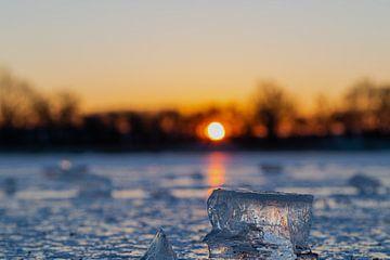 Eisbrocken auf einem gefrorenen See während eines warmen Sonnenaufgangs von Kim Willems