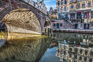 Brug in Utrecht met ochtendlicht en gespiegeld in stilstaand water. van Harrie Muis