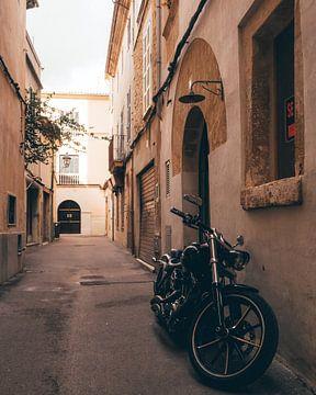 Motorradfahren in den traditionellen Straßen des historischen spanischen Dorfes Pollença auf Mallorc von Michiel Dros