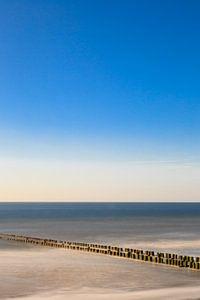 Golfbreker aan het strand in het water. van