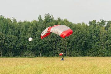 Landende parachutist in een weiland van