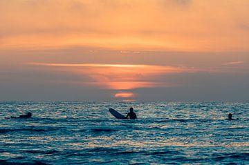 Surfers bewonderen de zonsondergang in het water bij Terschelling van Alex Hamstra