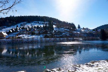 Kleines Dorf im Winter an einem zugefrorenen See von creativcontent