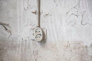 Ouderwets stopcontact aan een beschadigde muur in een verlaten schoolgebouw