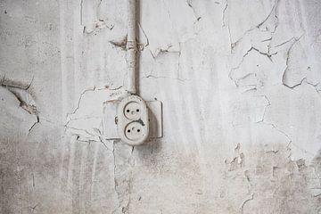 Ouderwets stopcontact aan een beschadigde muur in een verlaten schoolgebouw van Sjoerd van der Wal