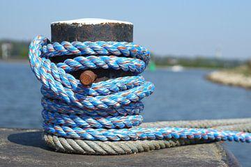 Roestige bolder met blauw scheepstouw aan het water van Maarten Pietersma