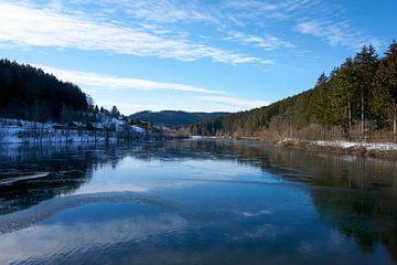 Bevroren rivier met sneeuw en ijs in zonneschijn onder blauwe hemel bij de Nagoldtalsperre van creativcontent