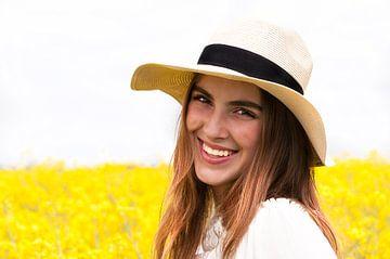 Portret van een jonge vrouw met een strohoed voor een geel bloemenveld van Anita Hermans