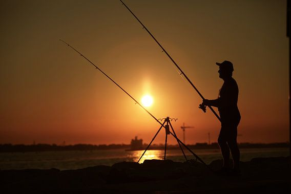 Visser bij zonsondergang aan Punta Sabbioni Italie