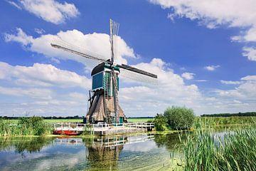 Caractéristique moulin à vent hollandais près de canal avec une végétation luxuriante sur Tony Vingerhoets
