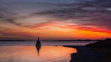Oude meerpaal met zonsopkomst van