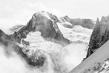 Ruige vergletsjerde bergtop steekt boven de wolken uit in zwart wit van Hidde Hageman