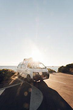 Een camper die staat geparkeerd langs de kust bij zonsondergang in Australie van Guido Boogert