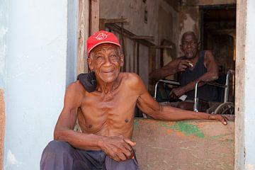 Deux Cubains devant et dans la maison