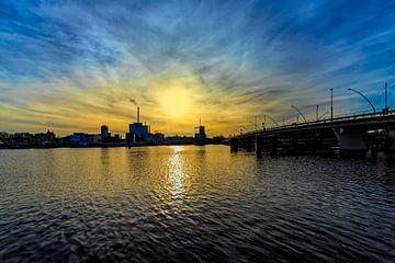 zicht op een rivier , met grote brug bij ondergaande zon