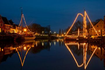 Traditionelle beleuchtete Segelschiffe im Hafen von Dokkum am Weihnachtsabend von Nisangha Masselink