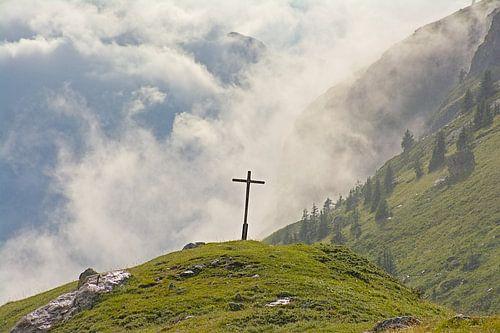 Kruis in een mistig Alpen landschap