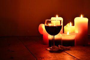 Wijnglas gevuld met rode wijn en kaarslicht in het donker.