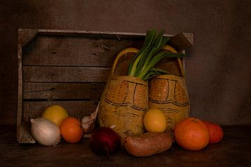 stilleven met klompen in een oud houten kist met fruit