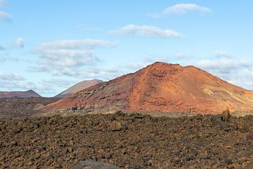Lavafeld und roter Berg im Hintergrund auf Lanzarote von Reiner Conrad