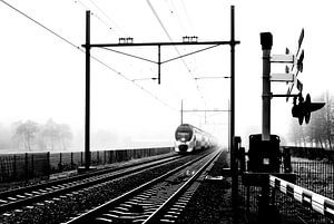 Zwart-wit foto van een Hollandse trein in mist bij spoorwegovergang van