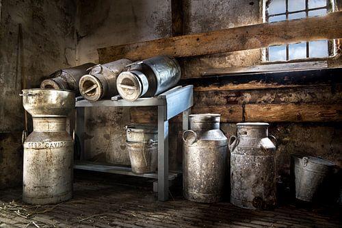 Verzameling melkbussen in een schuur. van
