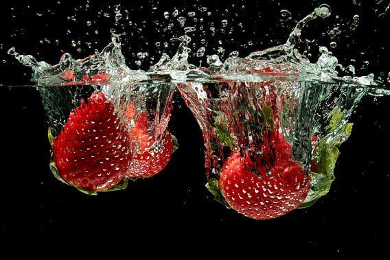 Aardbeien splashen in water van nilaya van vliet