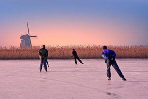 Schaatsen op het platteland van Nederland bij zonsondergang van