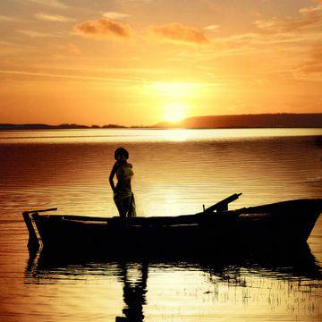 Vrouw in Boot bij zonsondergang (woman in boat) van Cor Heijnen