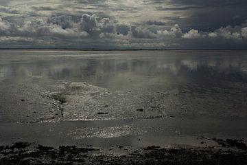 Wolkenluchten boven het drooggevallen Wad van