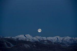 Volle maan boven besneeuwde bergtoppen